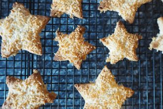 Cardamom coconut star biscuits on a wire baking rack