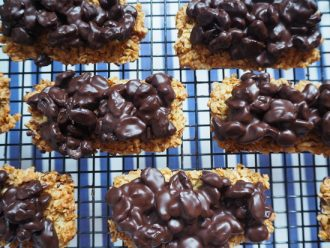 Close up of rectangular flapjack topped with dark chocolate raisins on a wire cooling rack with blue and white striped background