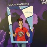 Blogger Becky Stafferton stood in front of Disneyland Paris purple run weekend back drop holding a blue selfie frame. She is wearing sparkly Minnie mouse ears and a red Disney half marathon run t-shirt and jeans. Her hair is in two plaits.