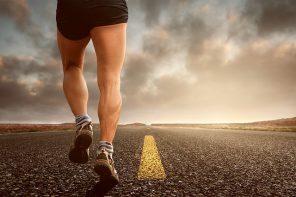 Botoom half of male runner wearing shorts running on a road