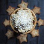 Small wooden bowl of sweet coconut hummus topped with sprinkled coconut. In the dark background are some star chaped cardamom coconut biscuits going around the bowl