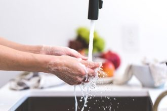 Close up of hands being washed under a running tap in a kitchen to show the importance of good personal hygiene
