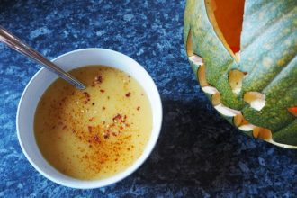 Boel of spicy pumpkin soup topped with chilli flakes next to a carved green jack o lantern