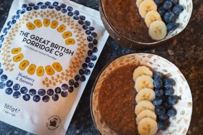 Packet of Blueberry & Banana The Great British Porridge Co. Porridge next to two bowls of porridge topped with sliced banana and blueberries