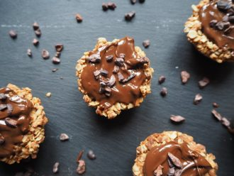 Close up of round triple chocolateprotein flapjack bites on a dark slate grey background