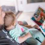 Dad looking at a picture book with a baby on his lap trying to establish a good bedtime routine