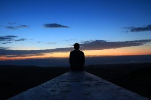 man sitting at the end of a pier. It is dusk and the sun has recently set, the sky is dark blue fading to orange down to the dark water in front of him. He is contemplating his life and thiking about quitting a bad habit.