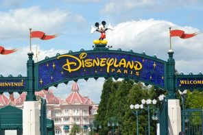 The Disneyland Paris welcome sign with the Disney Hotel in the background