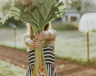 Blonde haired lady in a black and white striped dress holding out a bing bunch of rhubarb so that it covers her face. She looks as if she is stood in an allotment and is showing people how you can take better care of your health