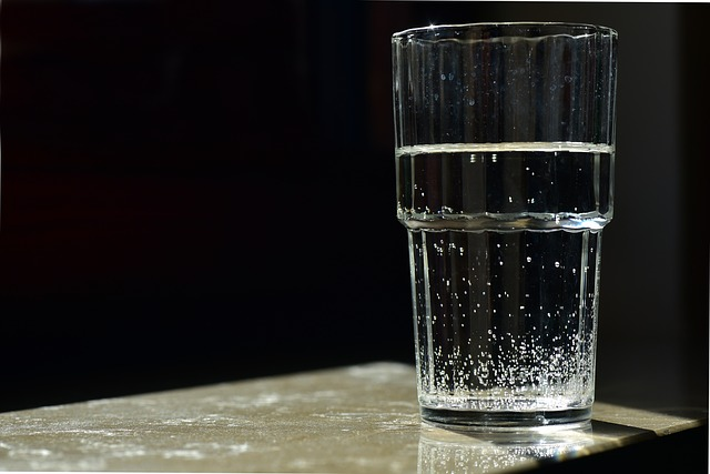 Glass of water set against a black background indicating the risk of contaminated water