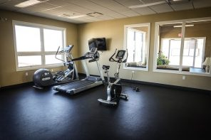 Three exercise machines positioned in the corner of an emoty fitness studio - a treadmill, exercise bike and cross trainer