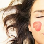Close up of half a young brunette lady's face. her eye is closed and her hair is spread out on a white sheet. She has a rose petal that looks like a sliced strawberry on her cheek and forehead.