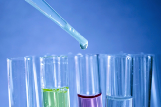 close up of 4 test tubes filled with different coloured fluid and a pipette dropping something into one of them