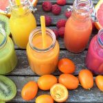 5 brightly covered smoothies in glass bottles with straws. surrounded by fresh fruits. rainbow food for detox