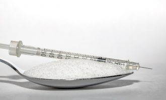 Close up of a teaspoon filled with sugar and in insulin injection is lying on top