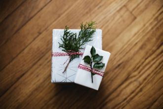 Two christmas presents stacked on top of one another. Wrapped in white natural paper and tied with a red patterned ribbon. here are evergreen leaves ticked in the ribbon.