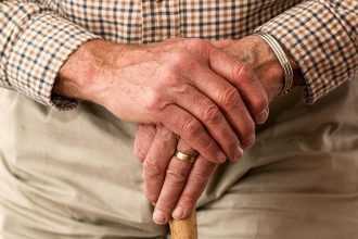 Close up of an elderly man's hands held over teh top of a walking stick. He has a gold wedding ring and is wearing light beige rousers and a brown checked shirt.