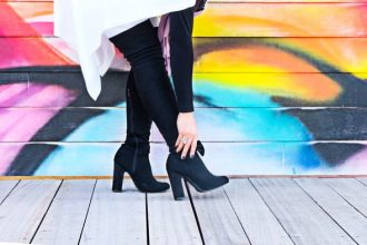 Woman's legs in black boots on a wooden floor against a graffiti background