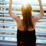 Back of a twenty something year old female. Her light brown hair is tied in a long ponytail and she is wearing a bacl vest which shows off the muscles in her back. Her arms are raised above her head and she is exercing on a series of metail bars to increase her upper body strength