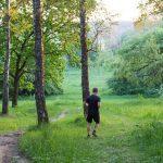 Man running through a grassy forest