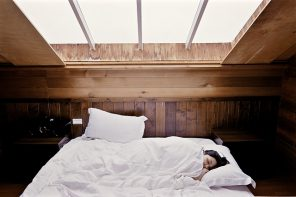 dark haired woman lying diagonally in bed with her head poking out of a white duvet
