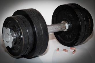 Dumbbells woth 4 capsules of steroid tablets next to them