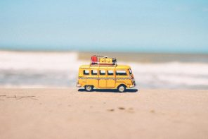 Child's camper van toy with mini luggage on it's roof on the sand with the sea in the background