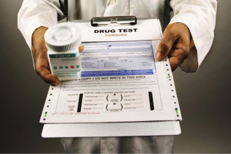 Close u up for a medical drug test form on a clipboard being held by a doctor who is also holding a jar of pills