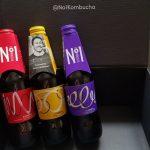Three bottle of No1 Kombucha propped up against a black box