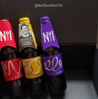 Three bottle of No1 Kombucha propped up against a black box