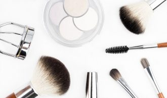 Selection of make up brushes and beauty tools laid out on a bright white background