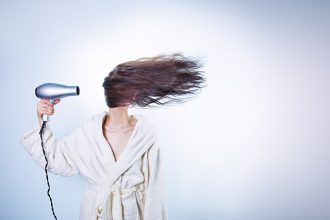 Long haired brunette woman stood to the left hand side of a white background. She is wearing a cream dresing gown and holding a silver hairdryer on her right hand. the hair dryer is blowing her hair all across her face so you can't see her face at all