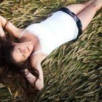 Long haired brunette lady lying on her back in a field of cut grain