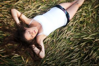 Long haired brunette lady lying on her back in a field of cut grain