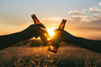 silhouette of two hands holding two beer bottles that are being touched together in cheers. Background is a bright orange sunset.