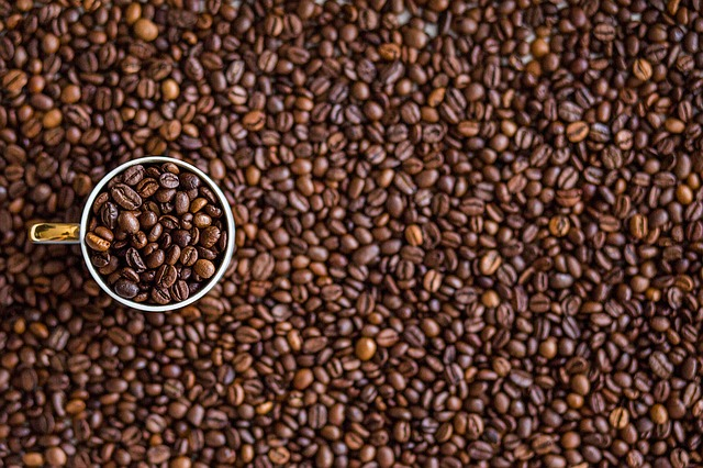 Background filled with coffee beans and a single cup is sat on top on the left hadn side, also filled with coffee beans