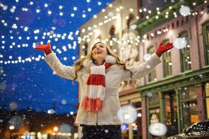 Blond haired woman stood outsode underneath Christmas firy lights.