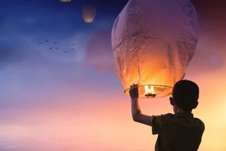 Silhouette of a boy holding a chinese lantern at new year waiting to release it with the other ones that are floating away at sunset