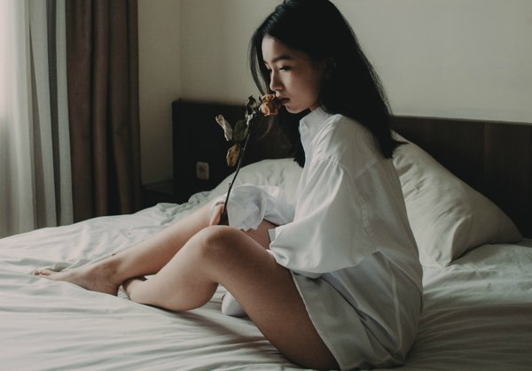 Asian girl in her 30s wearing just a whote shirt sat on a bed and she is sniffing a single rose