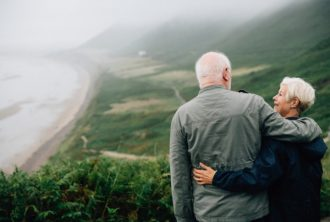senior citizen couple embracinf in front of a hillside beach and loving life