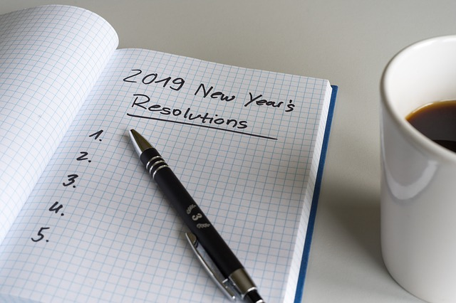 Notebooked opened up with the words 2019 New Year's Resolutions written and underlined on it.
