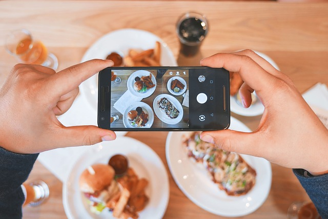 someones hands holding a phone in frojnt of a tabkle of food taking a picture of it to capture the future of food