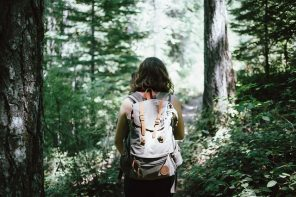 back of a long haired young brunette lady with a backpack on her back. She is going for a hike in a sunlit forest.