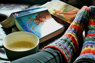 close up of a womans feet in brightly coloured striped woolen socks on a bed with two open books and a cup of coffee next to her.
