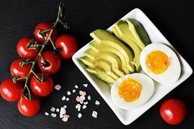 Examples of keto foods laid out on a white square plate on a black background. Includes vine tomatoes, cliced avocado and halved hard boiled egg