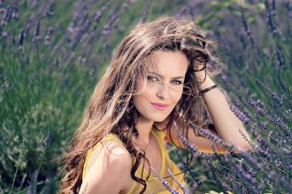 Long haired brunnete lady in her early thirties in a field of lavendar. She is a natural beauty.