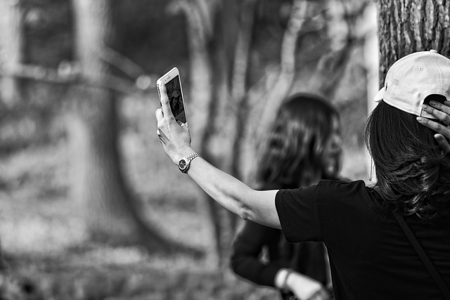 black and white photo of a long haired brunette lady taking a selfie