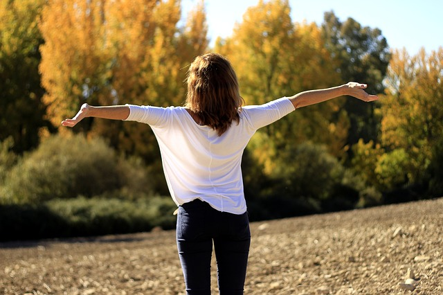 The back of a woman stood outside with her arms outstretched with joy. She is wearing dark jeans and a baggy white top and has long dark hair. she is stood in a field with autumn tress in front of her in the background of the picture