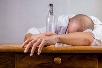 Man lat down leaning over a table with hid bald head restin gon his arms and hugging an empty bottle glass bottle. Suggesting he has drunk the alcoholic substance inside and is an alcoholic who needs help.