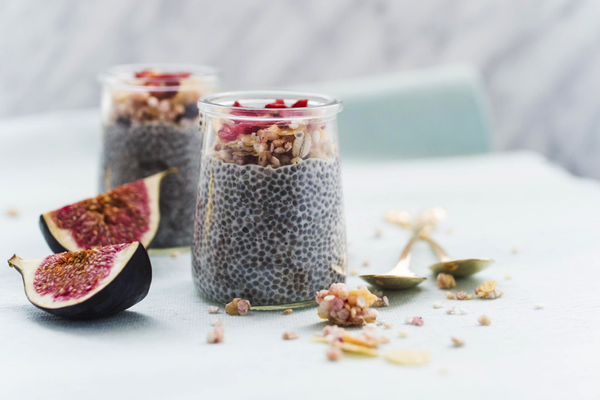2 pots of chia see pudding topped with nuts and figs set against a white background